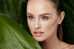 Schönheits-Frauen-Gesicht mit gesunder Haut und Grünpflanze lizenzfreie stockfotos