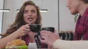Schönheits-Freunde, die den Kaffee, stehend im Café trinken in Verbindung stock video footage