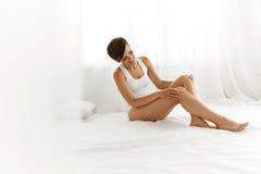 Schönheits-Körper-Frau Schönes Mädchen, das lange Beine Epilated berührt Stockbild