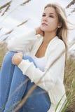 Schönheits-Mädchen, das im langen Gras auf Strand sitzt Stockfoto