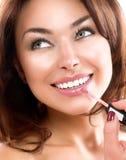 Schönheits-Mädchen, das Lipgloss anwendet Stockfotografie