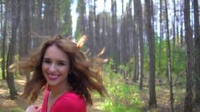 Schönheits-Mädchen im roten Kleid mit dem gesunden langen Haar im Waldporträt Glückliche Frau im Herbst in der Zeitlupe, lächelnd stock video footage
