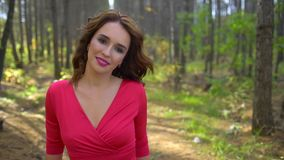 Schönheits-Mädchen im roten Kleid mit dem gesunden langen Haar im Waldporträt Glückliche Frau im Herbst in der Zeitlupe, lächelnd stock video
