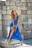 Schönheits-Modemädchenmodell im blauen Kleid, das auf Teil der Spalte aufwirft Stockbilder