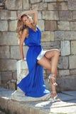 Schönheits-Modemädchenmodell im blauen Kleid, das auf Teil der Spalte aufwirft Lizenzfreies Stockfoto