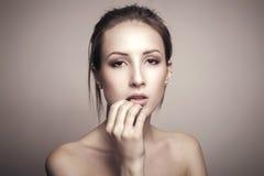 Schönheits-Porträt der schönen jungen Frau, die ihr Gesicht berührt stockfotografie