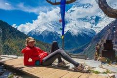 Schönheits-Reisend-Wanderer nehmen Rest-Gebirgsterrassen-Dorf Junges Mädchen, das lächelnde Kamera aufwirft Nordschnee-Spitzen Stockfotos