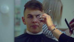Schönheits-Saal friseursalon Stilist macht einem jungen hübschen Kerl Haarschnitt Der Kerl sitzt in einem Stuhl und schaut in stock video