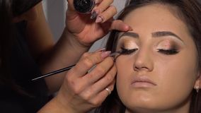 Schönheits-Saal Junges schönes Mädchenmodell sitzt im Stuhl Maskenbildner macht Mädchenmake-up Brunette in einer Schönheit stock video footage
