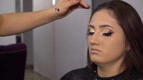 Schönheits-Saal Junges schönes Mädchenmodell sitzt im Stuhl Maskenbildner macht Mädchenmake-up Brunette in einer Schönheit stock footage