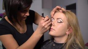 Schönheits-Saal Junges schönes Mädchenmodell sitzt im Stuhl Maskenbildner macht Mädchenmake-up Maskenbildner stock footage