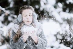 Schönheits-Winter-Mädchen-Schlagschnee in eisigem Winter Park draußen Fliegenschneeflocken Sonniger Tag stockfotos