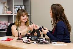 Schönheitsberater gibt dem Kunden eine Bürste für Wimpern Stockbilder
