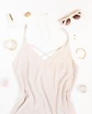 Schönheitsblogkonzept Frauen-Ausstattung Rosa Kleid, rosa Sonnenbrille, Armbänder, Halskette, Ohrringe und Kosmetik auf weißem Hi lizenzfreies stockfoto
