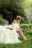 Schönheitsbraut, die ihre langen Beine in der Natur im Wald betrachtet Stockfotografie
