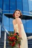 Schönheitsbraut im Brautkleid mit Blumenstrauß auf der Natur Lizenzfreie Stockbilder