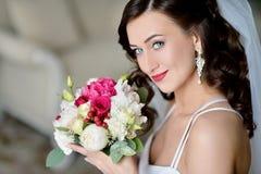 Schönheitsbraut im Brautkleid mit Blumenstrauß und Spitze verschleiern zuhause Lizenzfreies Stockbild