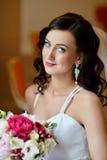 Schönheitsbraut im Brautkleid mit Blumenstrauß und Spitze verschleiern zuhause Stockbild