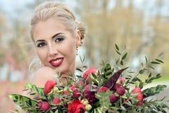 Schönheitsbraut im Brautkleid mit Blumenstrauß- und Spitzeschleier Lizenzfreie Stockfotos