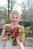 Schönheitsbraut im Brautkleid mit Blumenstrauß- und Spitzeschleier Stockfoto