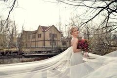 Schönheitsbraut im Brautkleid mit Blumenstrauß- und Spitzeschleier Stockfotos
