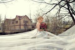 Schönheitsbraut im Brautkleid mit Blumenstrauß- und Spitzeschleier Stockbilder