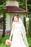 Schönheitsbraut im Brautkleid mit Blumenstrauß- und Spitzeschleier auf der Natur Schönes vorbildliches Mädchen in einem weißen Ho Lizenzfreies Stockfoto