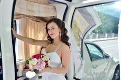 Schönheitsbraut im Brautkleid mit Blumenstrauß- und Spitzeschleier im Auto Stockfotografie
