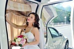 Schönheitsbraut im Brautkleid mit Blumenstrauß- und Spitzeschleier im Auto Stockbild