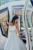 Schönheitsbraut im Brautkleid mit Blumenstrauß- und Spitzeschleier im Auto Lizenzfreies Stockbild