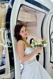 Schönheitsbraut im Brautkleid mit Blumenstrauß- und Spitzeschleier im Auto Stockfotos