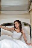 Schönheitsbraut im Brautkleid mit Spitzeschleier im Auto Stockfotos