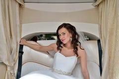 Schönheitsbraut im Brautkleid mit Spitzeschleier im Auto Lizenzfreie Stockbilder