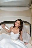 Schönheitsbraut im Brautkleid mit Spitzeschleier im Auto Lizenzfreie Stockfotografie
