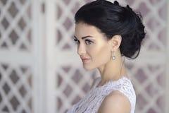Schönheitsbraut im Brautkleid zuhause Stockfotografie