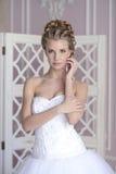 Schönheitsbraut im Brautkleid zuhause stockbild