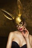 Schönheitsfrau über Goldhintergrund Stockfotos