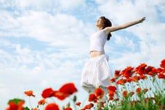 Schönheitsfrau auf dem Mohnblumegebiet Lizenzfreie Stockfotos