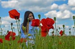 Schönheitsfrau auf dem Mohnblumengebiet von Blumen Stockfotografie