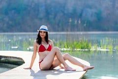 Schönheitsfrau in der roten Badebekleidung ein Sonnenbad nehmend auf dem Seepier lizenzfreies stockbild