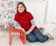 Schönheitsfrau an der Weihnachtsdekoration mit Schlitten Lizenzfreie Stockfotografie