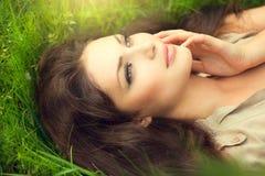 Schönheitsfrau, die auf dem Feld liegt Lizenzfreie Stockfotografie