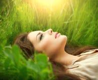 Schönheitsfrau, die auf dem Feld und dem Träumen liegt Stockfotografie