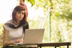 Schönheitsfrau, die den Laptop sitzt an einer Kaffeestube im Freien verwendet lizenzfreie stockfotos