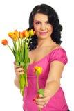 Schönheitsfrau, die eine frische Tulpe anbietet Lizenzfreies Stockbild