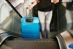 Schönheitsfrau, die ihr Gepäck auf Rolltreppe reist und hält stockfotografie