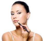 Schönheitsfrau, die Lippenstift anwendet Stockfoto