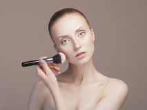 Schönheitsfrau, die Make-up anwendet Stockbild