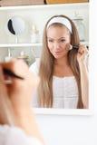 Schönheitsfrau, die an Make-up setzt stockbild