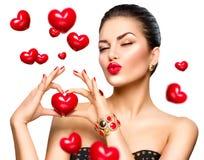 Schönheitsfrau, die rotes Herz in ihren Händen zeigt Stockfotografie